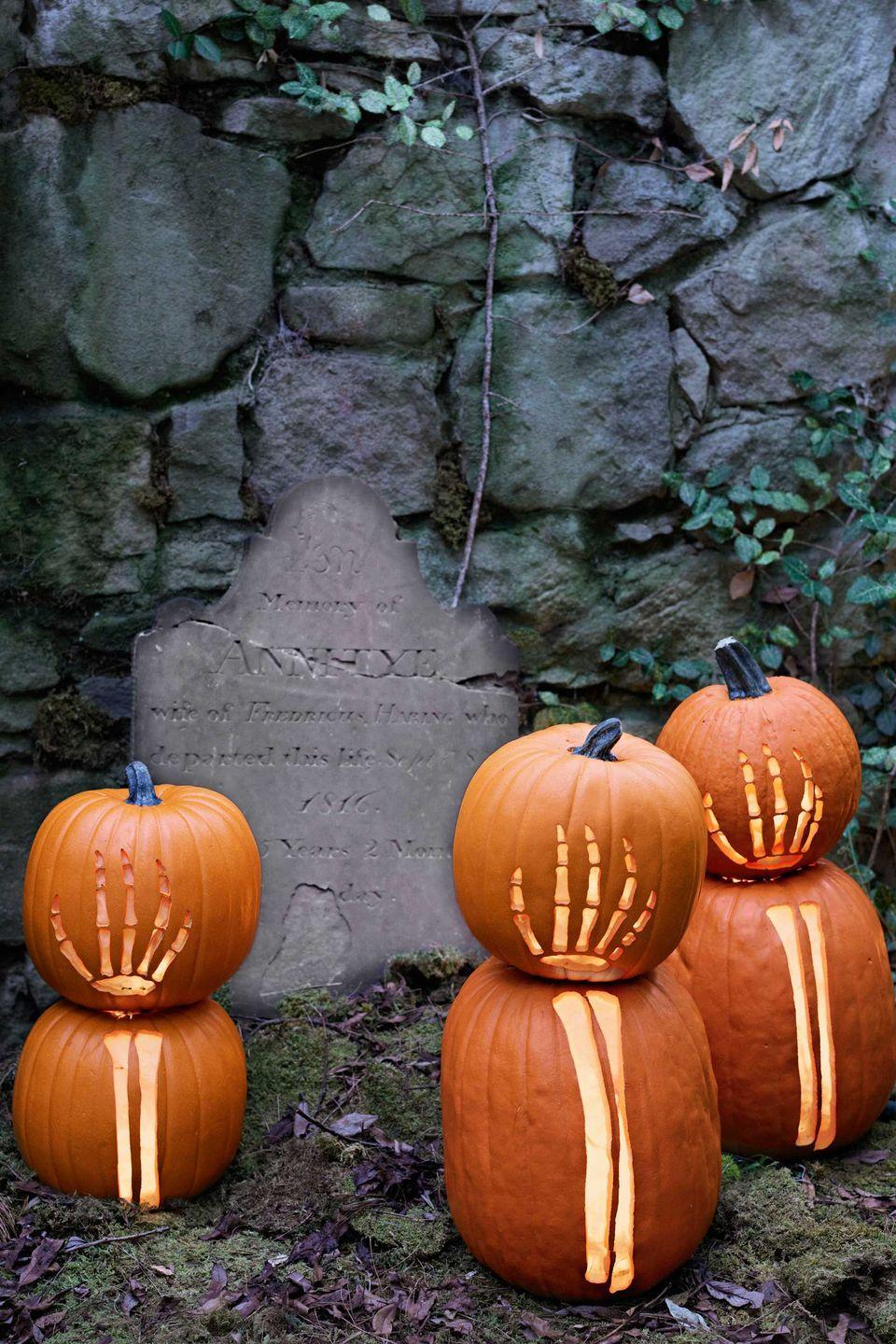 """<p>These carved pumpkins look as if they're reaching from beyond the grave in your front yard.</p><p><strong>Step 1:</strong> Select a pair of pumpkins to form each arm-hand combo. Determine which gourd will serve as the arm (usually the taller one) and trim its stem so the other pumpkin can rest securely on top. Carve a hole in the bottoms of both, scoop out the pulp, and return the cut pieces.</p><p><strong>Step 2:</strong> Print out our <a href=""""https://www.countryliving.com/diy-crafts/how-to/a3048/halloween-templates-1009/"""" rel=""""nofollow noopener"""" target=""""_blank"""" data-ylk=""""slk:skeletal templates"""" class=""""link rapid-noclick-resp"""">skeletal templates</a> and resize on a copier, scaling the images to fit your pumpkins.</p><p><strong>Step 3:</strong> Cut out stencils as directed on the templates and affix the arm stencil to the bottom pumpkin with masking tape. Trace on the design with a felt-tip pen. Repeat the process on the other pumpkin, using the hand template. </p><p><strong>Step 4:</strong> Remove stencils, then carefully carve along the drawn lines with an X-Acto knife. Affix a battery-operated votive candle in the base of each pumpkin with adhesive. </p>"""