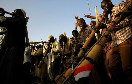 Sudanese demonstrators play traditional instruments during the sit-in protest outside Defence Ministry in Khartoum