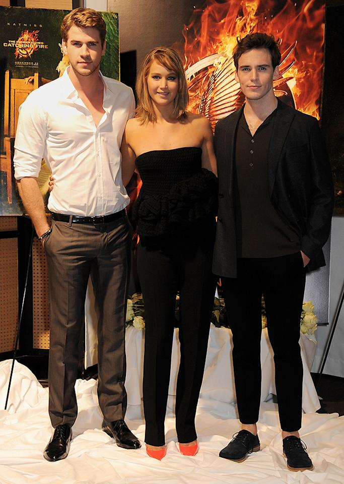 CANNES, FRANCE - MAY 18:  (EMBARGOED FOR PUBLICATION IN UK TABLOID NEWSPAPERS UNTIL 48 HOURS AFTER CREATE DATE AND TIME. MANDATORY CREDIT PHOTO BY DAVE M. BENETT/GETTY IMAGES REQUIRED)  (L to R) Actors Liam Hemsworth, Jennifer Lawrence and Sam Claflin attend The Hunger Games: Catching Fire photocall at the 2013 Cannes Film Festival at Majestic Barierre on May 18, 2013 in Cannes, France.  (Photo by Dave M. Benett/Getty Images for Lionsgate)