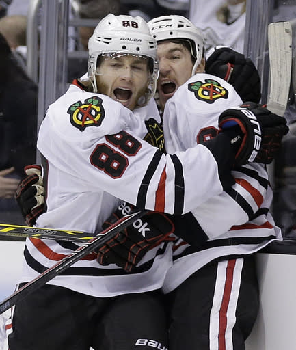 FILe - In this May 30, 2014 file photo, Chicago Blackhawks right wing Patrick Kane, left, celebrates his tie-breaking goal with center Andrew Shaw against the Los Angeles Kings during the third period of Game 6 of the Western Conference finals of the NHL hockey Stanley Cup playoffs in Los Angeles. The Blackhawks have agreed to eight-year contract extensions with captain JonathanToews and star forward Patrick Kane. General manager Stan Bowman said all along that the extensions were his biggest offseason priority, and the team announced the megadeals Wednesday, July 9, 2014. (AP Photo/Chris Carlson, File)
