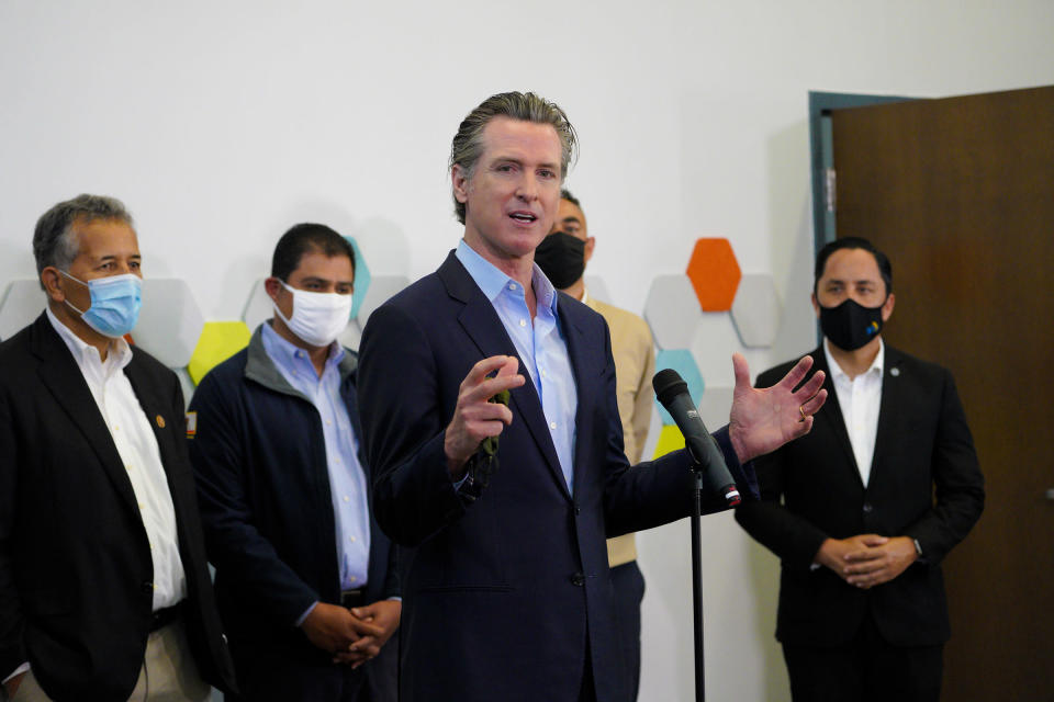Governor Gavin Newsom speaks with news reporters about San Diego's newest pop-up vaccination site at the Park de la Cruz Recreation Center in the City Heights neighborhood on Friday, April 2, 2021. Accompanying Newsom was Juan Vargas, Ben Hueso, Sean Elo-Rivera and Todd Gloria. (Nelvin C. Cepeda/The San Diego Union-Tribune via AP)