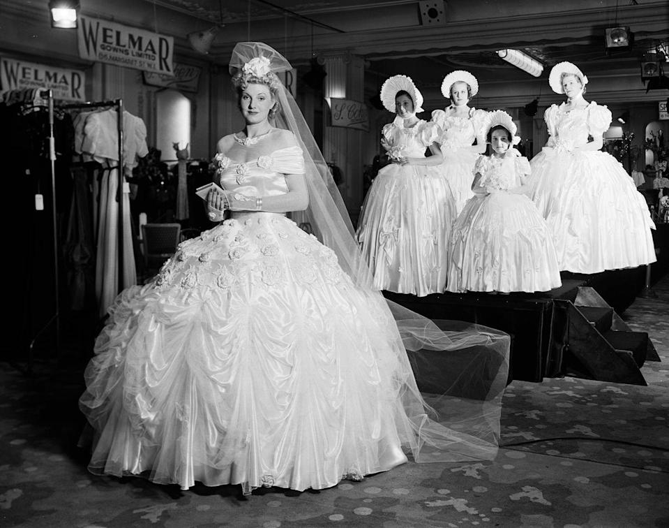 "<p>At Grosvenor House in London, a model shows off a luxury gown made of 48 yards of satin and 22 yards of tulle. On average, 1930s brides paid <a href=""http://qz.com/228518/the-venerable-80-year-tradition-of-the-insanely-expensive-american-wedding/#/h/82573,1,82577,2/"" rel=""nofollow noopener"" target=""_blank"" data-ylk=""slk:$1,092 in today's dollars"" class=""link rapid-noclick-resp"">$1,092 in today's dollars</a> for their dresses. </p>"