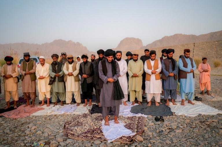 Taliban members pray together at dusk by the riverbed (AFP/Bulent KILIC)