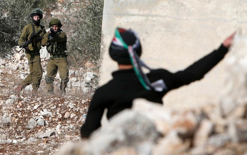 A Palestinian protester throws stones towards Israeli security forces during clashes near Nablus, in the occupied West Bank, on December 9, 2016