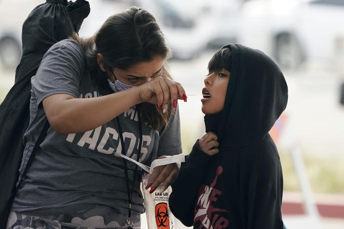 A boy is aided in taking a COVID-19 test on the Martin Luther King Jr. Medical Campus, Thursday, Jan. 7, 2021, in Los Angeles. (AP Photo/Marcio Jose Sanchez)