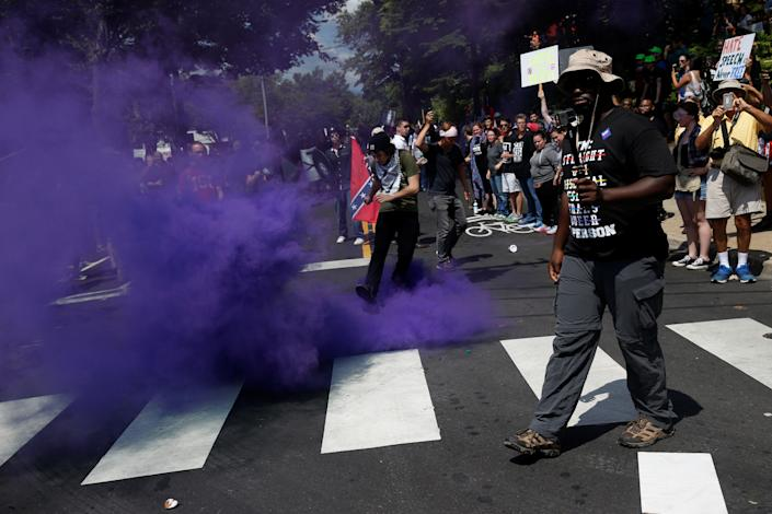 A smoke bomb is thrown at a group of counter-protesters.