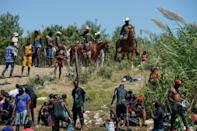 United States Border Patrol agents on horseback look on as Haitian migrants sit on the banks of the Rio Grande near Del Rio, Texas (AFP/PAUL RATJE)