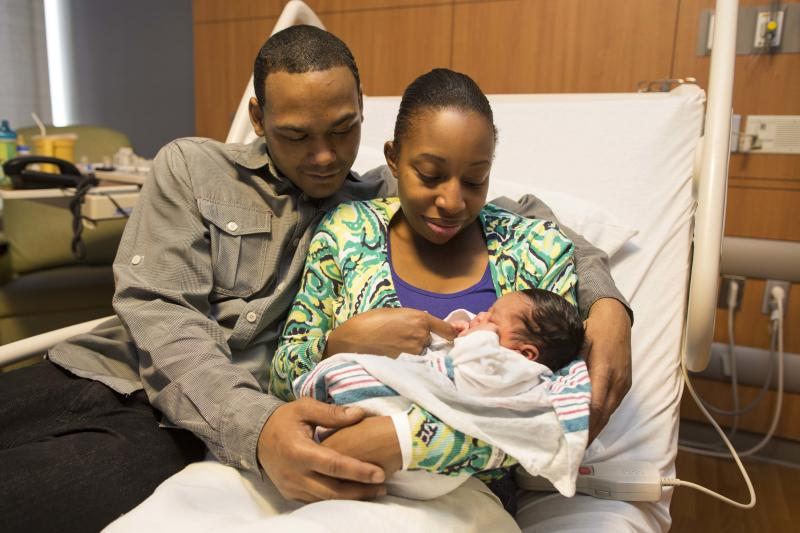 Marcus Ross, left, and his fiancé Melissa Jones hold their newborn daughter Mariah Faith Ross in her hospital room at Prentice Women's Hospital in Chicago. Jones couldn't make it inside of the hospital in time Thursday evening, and delivered Mariah in the family's minivan, just feet from the front door of Prentice Women's Hospital. (AP Photo/Scott Eisen)
