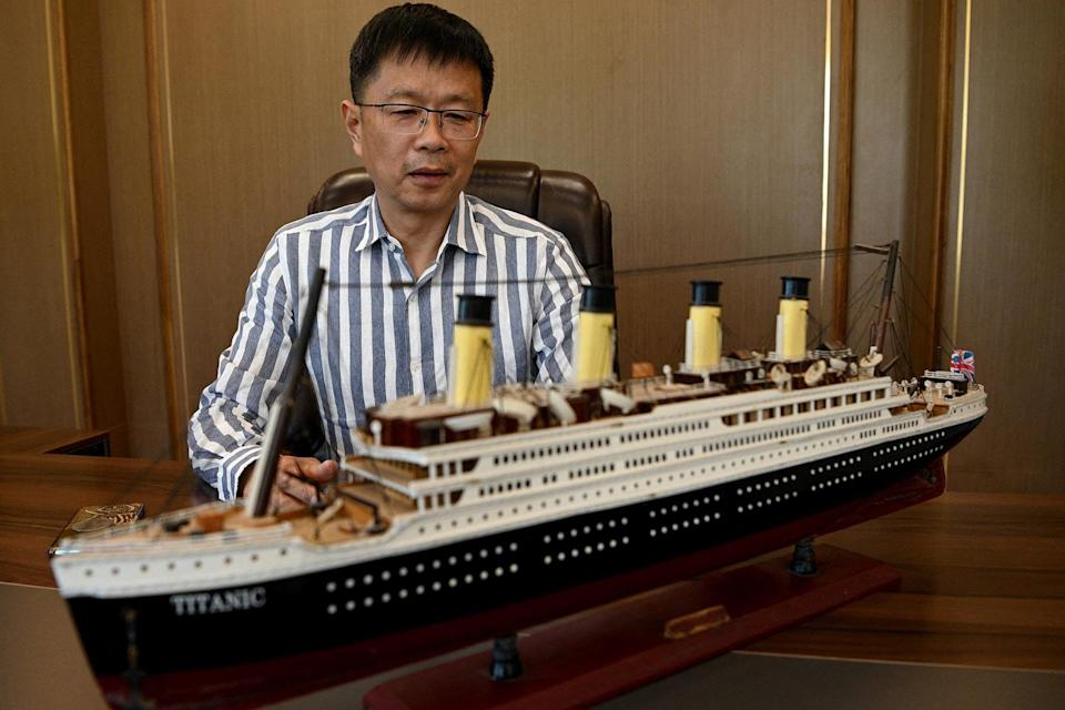 An investor helping to build a life-size replica of the Titanic, next to a model of the ship