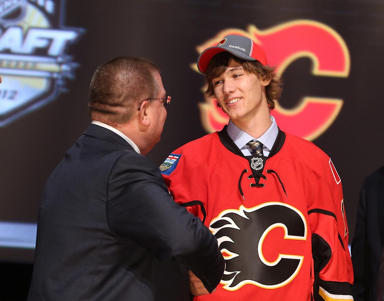 PITTSBURGH, PA - JUNE 22:  Mark Jankowski (R), 21st overall pick by the Calgary Flames, shakes hands with a Flames representative on stage during Round One of the 2012 NHL Entry Draft at Consol Energy Center on June 22, 2012 in Pittsburgh, Pennsylvania.  (Photo by Bruce Bennett/Getty Images)