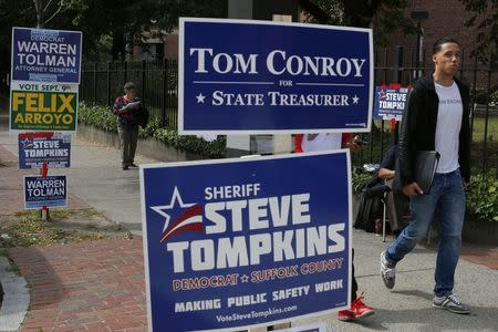 Pedestrians walk past signs with names of candidates outside a polling station on primary election day in Boston, Massachusetts September 9, 2014. REUTERS/Brian Snyder