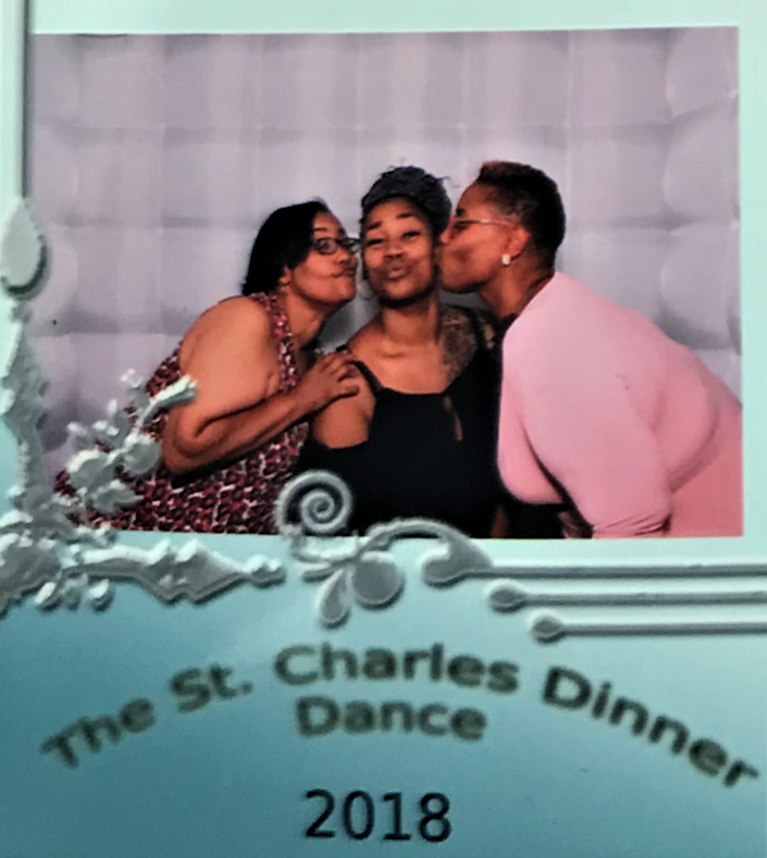 A woman, flanked by two others, blows a kiss. A sign below says The St. Charles Dinner Dance 2018