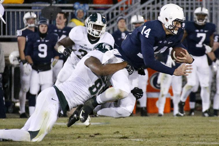 Penn State quarterback Christian Hackenberg (14) is tackled by Michigan State defensive end Shilique Calhoun (89) after scrambling for a short gain during the second half of an NCAA college football game in State College, Pa., Saturday, Nov. 29, 2014. Michigan State won 34-10. (AP Photo/Gene J. Puskar)