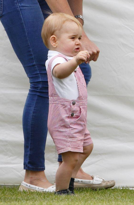 """<p>Prince George looked adorable in a pair of pink overalls while he watched his daddy, Prince William play in a charity polo match at Cirencester Park Polo Club on June 15, 2014.</p><p><strong>More:</strong> <a href=""""https://www.townandcountrymag.com/society/tradition/g10044961/prince-george-photos-news/"""" rel=""""nofollow noopener"""" target=""""_blank"""" data-ylk=""""slk:The Cutest Photos of Prince George"""" class=""""link rapid-noclick-resp"""">The Cutest Photos of Prince George</a></p>"""