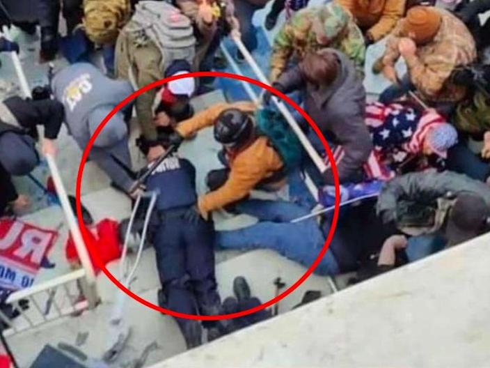 Jeffrey Sabol holds a police baton and his hand on a Capitol police officer who had been dragged down a set of stairs during the insurrection at the US Capitol. He has been arrested and is facing five years in prison. (FBI)