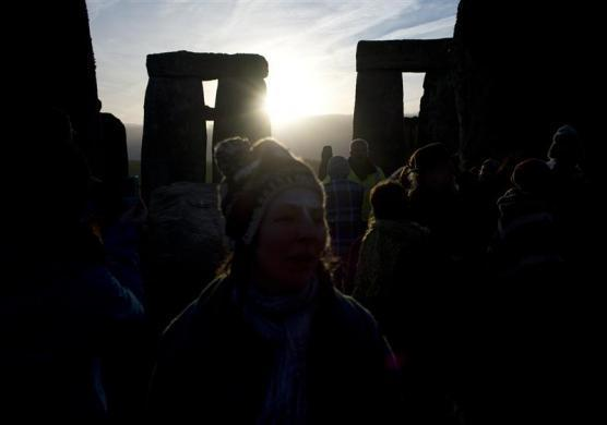 Revellers watch as the sun rises at Stonehenge on Salisbury plain in southern England December 22, 2011. The winter solstice is the shortest day of the year, and the longest night of the year.