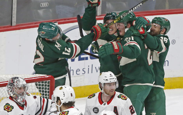 Minnesota Wild's Ryan Suter, second from right, is mobbed by teammates after scoring against Chicago Blackhawks goalie Cam Ward, lower left, to tie the score during the third period of an NHL hockey game Thursday, Oct. 11, 2018, in St. Paul, Minn. The Wild won 4-3 in overtime. (AP Photo/Jim Mone)