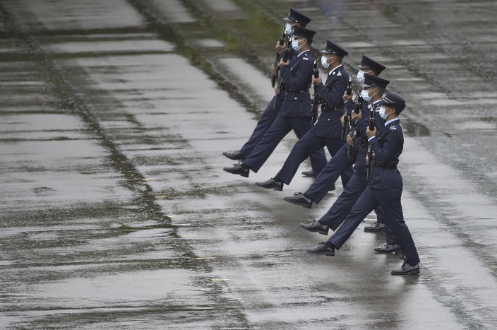 """Hong Kong police show their new goose step marching style on the National Security Education Day at a police school in Hong Kong Thursday, April 15, 2021. Authorities in Hong Kong are marking the day with a police college open house, where police personnel demonstrated the Chinese military's """"goose step"""" march, replacing British-style foot drills. The """"goose step"""" march is one in which troops swing their legs off the ground in unison, keeping each leg straight. (AP Photo/Vincent Yu)"""