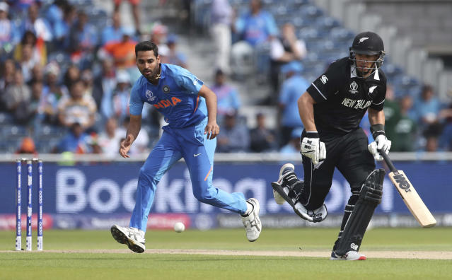 India's Bhuvneshwar Kumar, left, runs to field the ball after a shot played by New Zealand's Tom Latham during the Cricket World Cup semi-final match between India and New Zealand at Old Trafford in Manchester, England, Wednesday, July 10, 2019. (AP Photo/Aijaz Rahi)