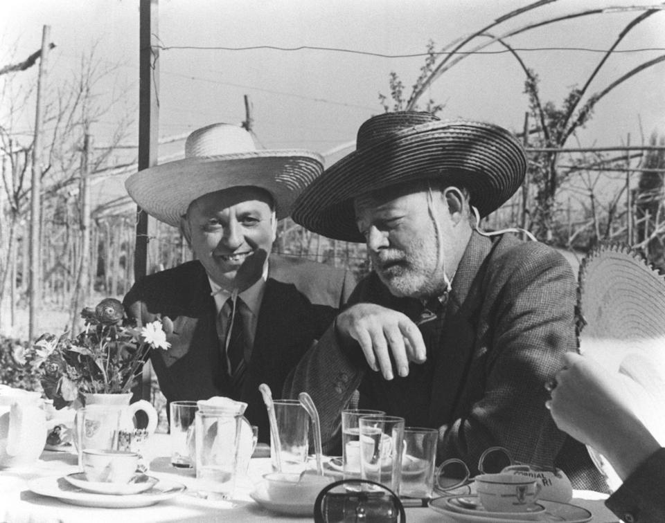 <p>Wearing playful cowboy hats, Hemingway enjoys a leisurely lunch with his friend Giuseppe Cipriani in Venice, Italy. </p>