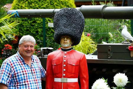 """Gary Blackburn, a 53-year-old tree surgeon from Lincolnshire, Britain, poses with a model of the Queen's Coldstream Guard at his British curiosities collection called """"Little Britain"""" in Linz-Kretzhaus, south of Germany's former capital Bonn, Germany, August 24, 2017. REUTERS/Wolfgang Rattay"""