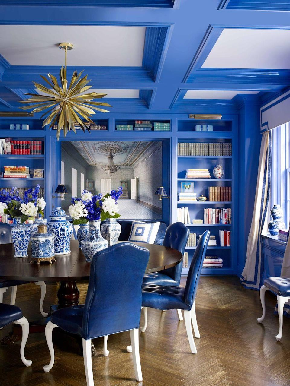 """<p>For a Manhattan dining room, designer <a href=""""http://www.kembleinteriors.com"""" rel=""""nofollow noopener"""" target=""""_blank"""" data-ylk=""""slk:Celerie Kemble"""" class=""""link rapid-noclick-resp"""">Celerie Kemble</a> carried the vibrant blue on the walls, a custom color by <a href=""""https://www.finepaintsofeurope.com"""" rel=""""nofollow noopener"""" target=""""_blank"""" data-ylk=""""slk:Fine Paints of Europe"""" class=""""link rapid-noclick-resp"""">Fine Paints of Europe</a>, up to the ceiling's coffering, which makes a graphic statement. The dining table is from <a href=""""https://centuryfurniture.com"""" rel=""""nofollow noopener"""" target=""""_blank"""" data-ylk=""""slk:Century"""" class=""""link rapid-noclick-resp"""">Century</a>, and the light fixture is by Tony Duquette for <a href=""""http://www.remains.com"""" rel=""""nofollow noopener"""" target=""""_blank"""" data-ylk=""""slk:Remains Lighting"""" class=""""link rapid-noclick-resp"""">Remains Lighting</a>. </p>"""
