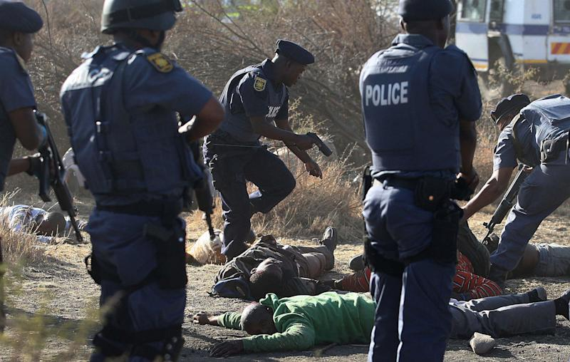 FILE - In this photo taken Thursday, Aug. 16, 2012 Police surround the bodies of striking miners after opening fire on a crowd  at the Lonmin Platinum Mine near Rustenburg, South Africa. The state of South Africa's police forces came into sharp focus last week during Pistorius' bail hearing where police stumbled and fumbled in the bail hearing of Pistorius who is charged with the shooting death of his girlfriend Reeva Steenkamp. The judicial system and its ruthless police force was the backbone of the racist Apartheid system. Now, almost two decades after Mandela ended the all-white regime in 1994, this system is creaking under corruption and mismanagement. (AP Photo/File)