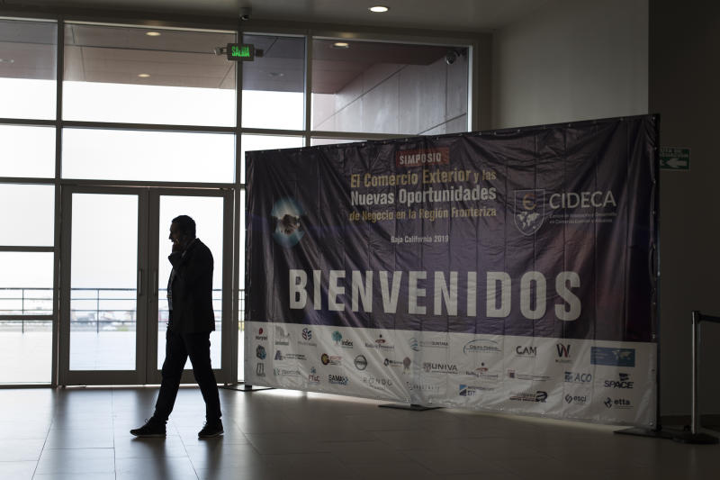 "A business man talks on the phone next to the welcome sign of the ""New Opportunities for Foreign Trade"" Symposium at the Rosarito Convention Center near Tijuana, Mexico, Friday, June 7, 2019. Companies have been rushing to ship as many goods as possible out of Mexico to get ahead of possible tariffs threatened by President Donald Trump, hurriedly sending cars, appliances and construction materials across the border to beat Monday's deadline. (AP Photo/Hans-Maximo Musielik)"
