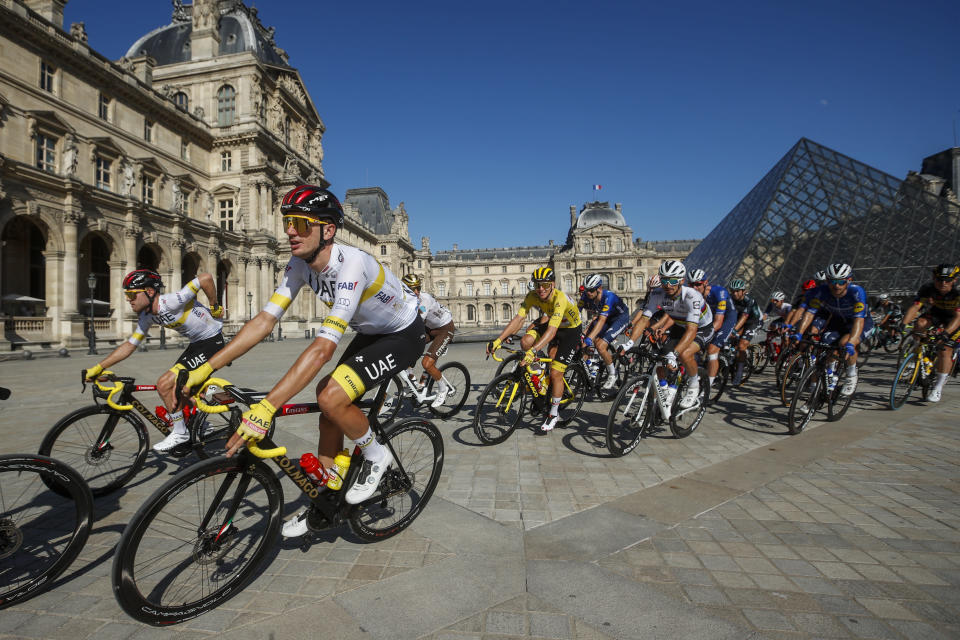 Slovenia's Tadej Pogacar, wearing the overall leader's yellow jersey, rides in front of The Louvre Museum with his UAE Team Emirates teammates during the twenty-first and last stage of the Tour de France cycling race over 108.4 kilometers (67.4 miles) with start in Chatou and finish on the Champs Elysees in Paris, France, Sunday, July 18, 2021. (Yoan Valat/Pool Photo via AP)