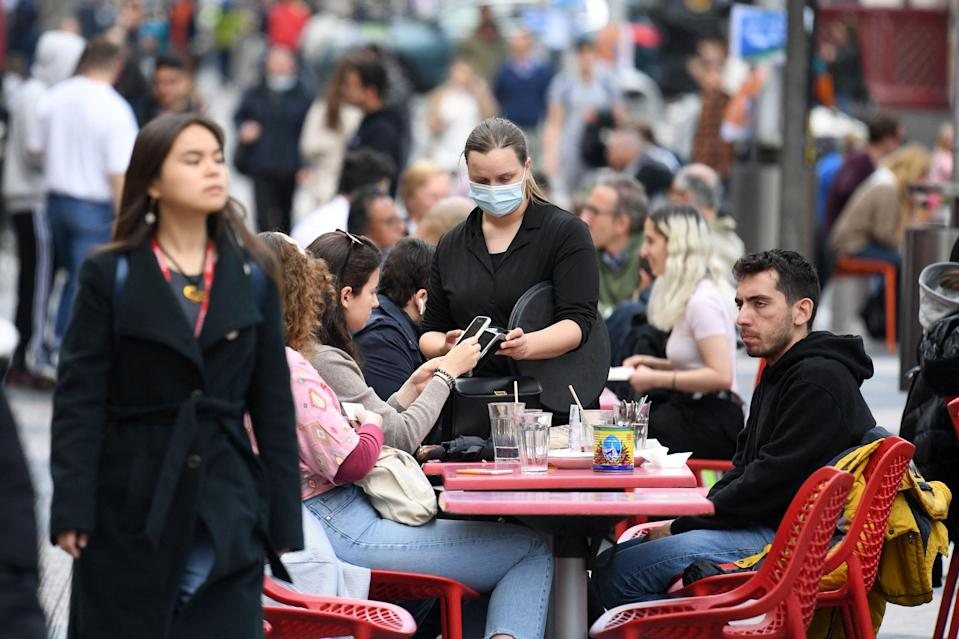 <p>People enjoy refreshments at tables set up outside a cafe in south Kensington</p> (AFP via Getty Images)