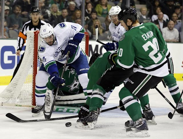 Vancouver Canucks' Ryan Kesler (17) makes a pass as Dallas Stars' Brenden Dillon, center, and Cody Eakin (20) help defend the net during the second period of an NHL hockey game, Thursday, Dec. 19, 2013, in Dallas. (AP Photo/Tony Gutierrez)