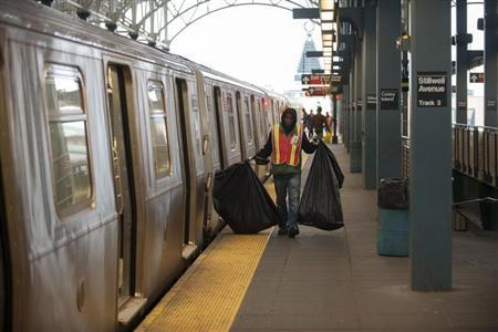 A custodian carries bags of garbage as New York City subway trains stop at the Coney Island station prior to a total subway shutdown in New York