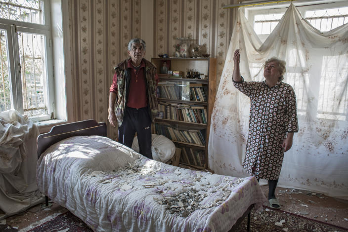 Nazile Tehmezova, right, and her husband Ramiz Huseyinov inspect the damage to their house following overnight shelling by Armenian forces, in the city of Terter, Azerbaijan, Thursday, Oct. 15, 2020. The conflict between Armenia and Azerbaijan continues for a third week despite a Russia-brokered cease-fire deal, as both sides exchanged accusations and claims of new attacks over the separatist territory of Nagorno-Karabakh. (Can Erok/DHA via AP)