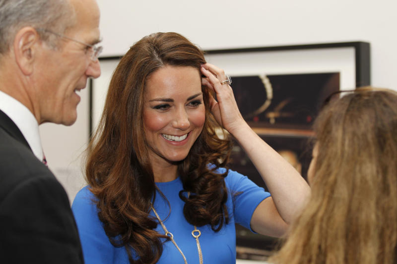 Kate, Duchess of Cambridge reacts as she talk to photographer Jillian Edelstein, right, during her visit to 'Road to 2012 : Aiming High' exhibition at the National Portrait Gallery in London, Thursday, July 19, 2012. The Duchess of Cambridge is the Patron of the National Portrait Gallery. The exhibition showcase commissioned photographs documenting the preparations for London 2012 Olympics. (AP Photo/Sang Tan, Pool)