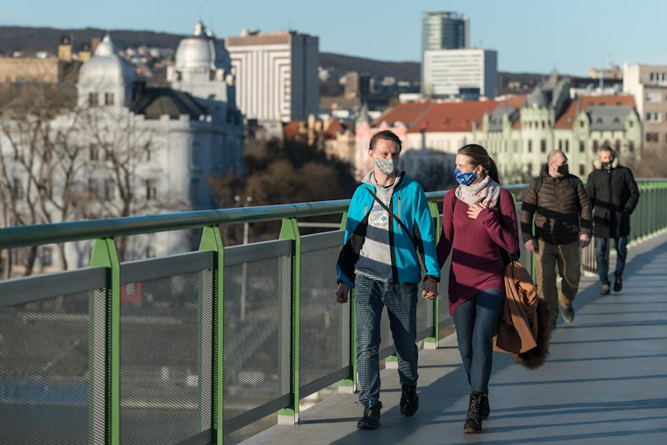 A young couple wearing face masks as a preventive measure against the spread of coronavirus walks along the Old Bridge in Bratislava. The lockdown declared by the government will last until 7th of February. (Photo by Tomas Tkacik / SOPA Images/Sipa USA)