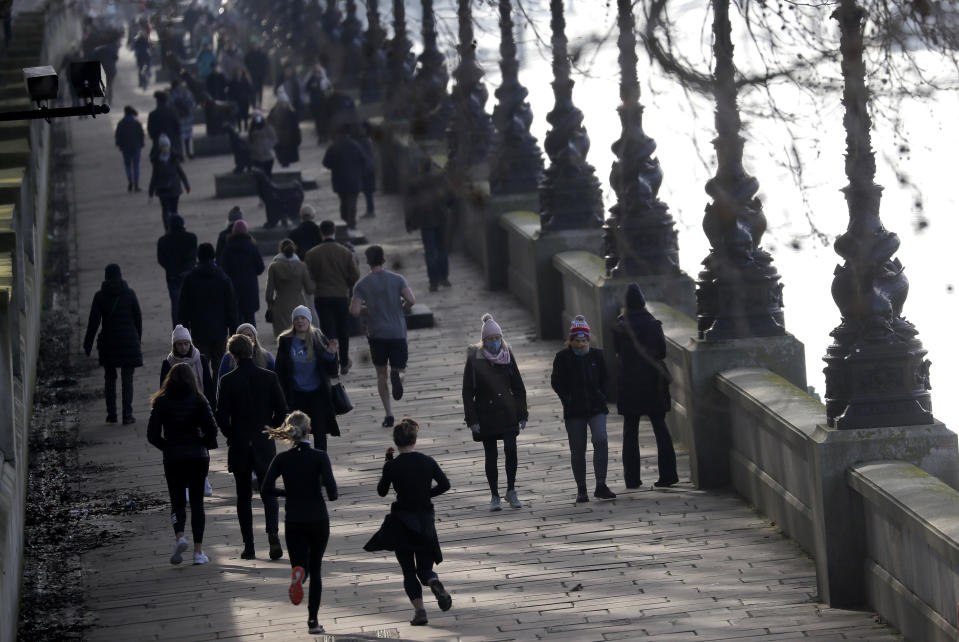 People exercise along the bank of the River Thames in London, Saturday, Jan. 23, 2021 during England's third national lockdown since the coronavirus outbreak began. The U.K. is under an indefinite national lockdown to curb the spread of the new variant, with nonessential shops, gyms and hairdressers closed, and people being told to stay at home. (AP Photo/Kirsty Wigglesworth)