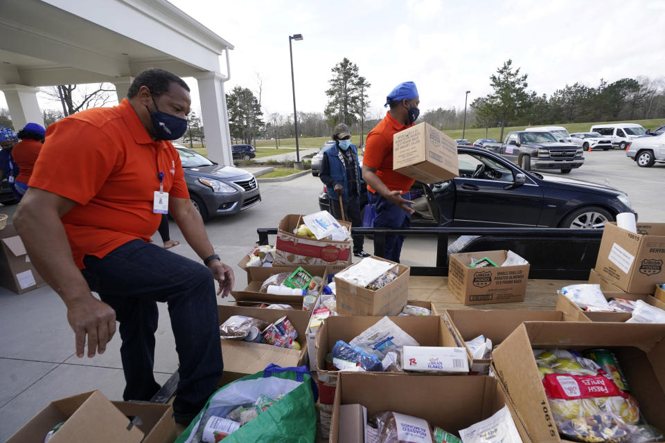 Mississippi SHINE Project team members distribute boxes loaded with a variety of staples, dried foods, powered milk, small blocks of cheese, canned vegetables, dried beans and apples to residents at the Jefferson Comprehensive Health Center in Fayette, Miss., on Friday, March 12, 2021. Over 100 boxes of donated food were distributed within an hour to residents of one of the poorest counties in the state. (AP Photo/Rogelio V. Solis)