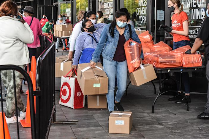 People receive a food bank donation at the Barclays Center on May 15, 2020 in the Brooklyn borough in New York City. (Photo by Stephanie Keith/Getty Images)