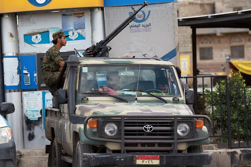 Shiite Huthi militiamen sit on a pick-up truck mounted with a heavy machine-gun in the Yememi capital Sanaa on March 26, 2015 (AFP Photo/Mohammed Huwais)