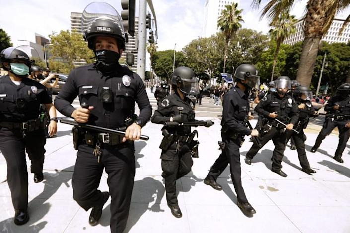 LOS ANGELES, CA - AUGUST 14, 2021 - - Los Angeles police officers go to separate advocates against vaccine mandates and pro-vaccine advocates in front of the L.A.P.D. Headquarters in downtown Los Angeles on August 14, 2021. A man was stabbed during the melee and taken by paramedics to a nearby hospital. No arrests were made in the confrontation. (Genaro Molina / Los Angeles Times)