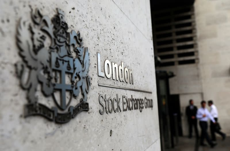 Pedestrians leave and enter the London Stock Exchange in London