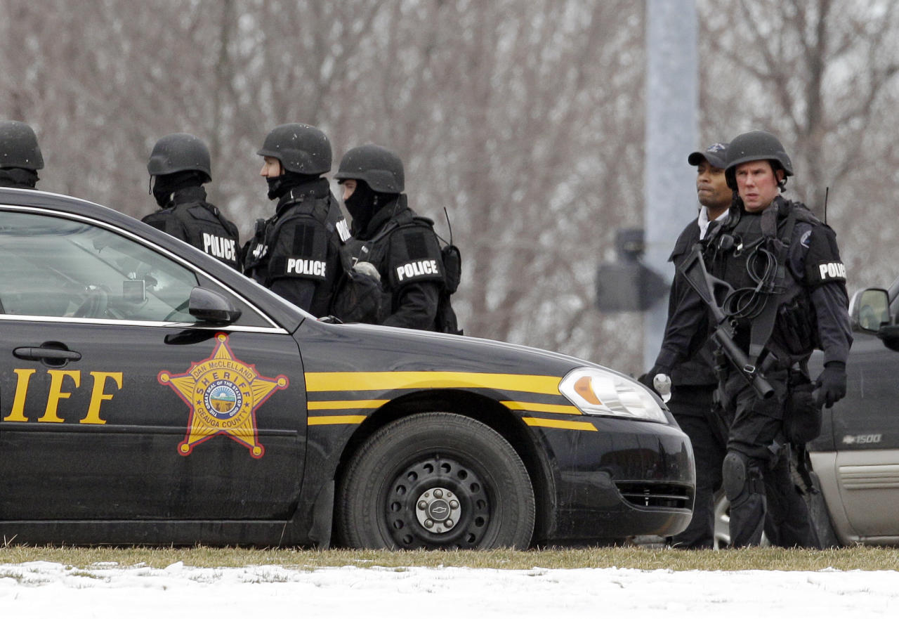 S.W.A.T. members leave Chardon High School in Chardon, Ohio Monday, Feb. 27, 2012. A gunman opened fire inside the high school's cafeteria at the start of the school day Monday, wounding five students, officials said. Special Agent Vicki Anderson said Monday the shooter was taken into custody near his car about half a mile away from the high school. A spokeswoman for the Cleveland Clinic confirmed five students were being treated at two different hospitals. (AP Photo/Mark Duncan)