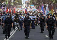 Hundreds of protesters march behind a row of police in Sydney, Saturday, March 6, 2021, ahead of the annual Gay and Lesbian Mardi Gras. The protesters say they want to restore the protest roots of Mardi Gras and challenge systems of injustice. (AP Photo/Rick Rycroft)