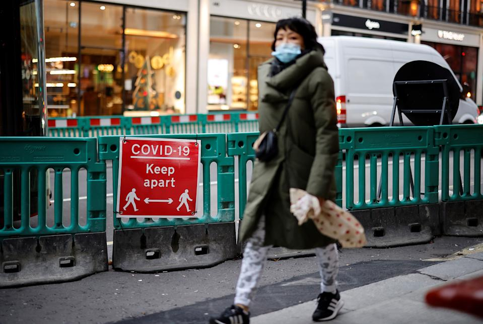 A pedestrian wearing a face mask or covering due to the COVID-19 pandemic, walks past a COVID-19 sign asking people to social distance as they walk on Oxford Street in central London on December 22, 2020. - UK government borrowing continued to soar in November on emergency action to support the virus-hit economy which nevertheless rebounded stronger than expected in the third quarter, official data showed Tuesday. Government borrowing last month hit £31.6 billion ($41.8 billion, 34.2 billion euros), a record for November -- taking public sector net debt to £2.1 trillion, the Office for National Statistics said in a statement. (Photo by Tolga Akmen / AFP) (Photo by TOLGA AKMEN/AFP via Getty Images)