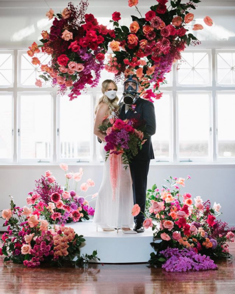 Couple on a floral stage in their bride and groom outfits and face masks
