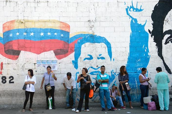 People stand by a mural of Hugo Chavez in Petare (AFP Photo/Federico Parra)