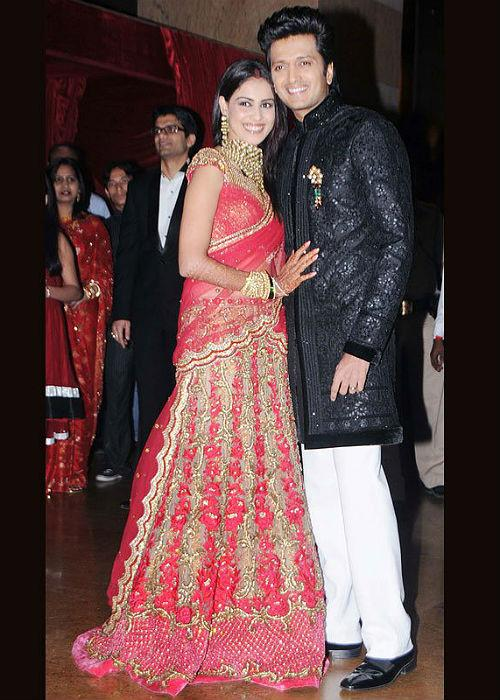 <b>8. Genelia: </b><br>Genelia wore a red lehenga-choli ensemble and net dupatta heavily decorated with golden embroidery and sequins, exuding classic elegance. The red and gold stunning lehenga was designed by Shane and Falguni Peacock. The fitted choli and flairs of the lehenga suited her slim figure.