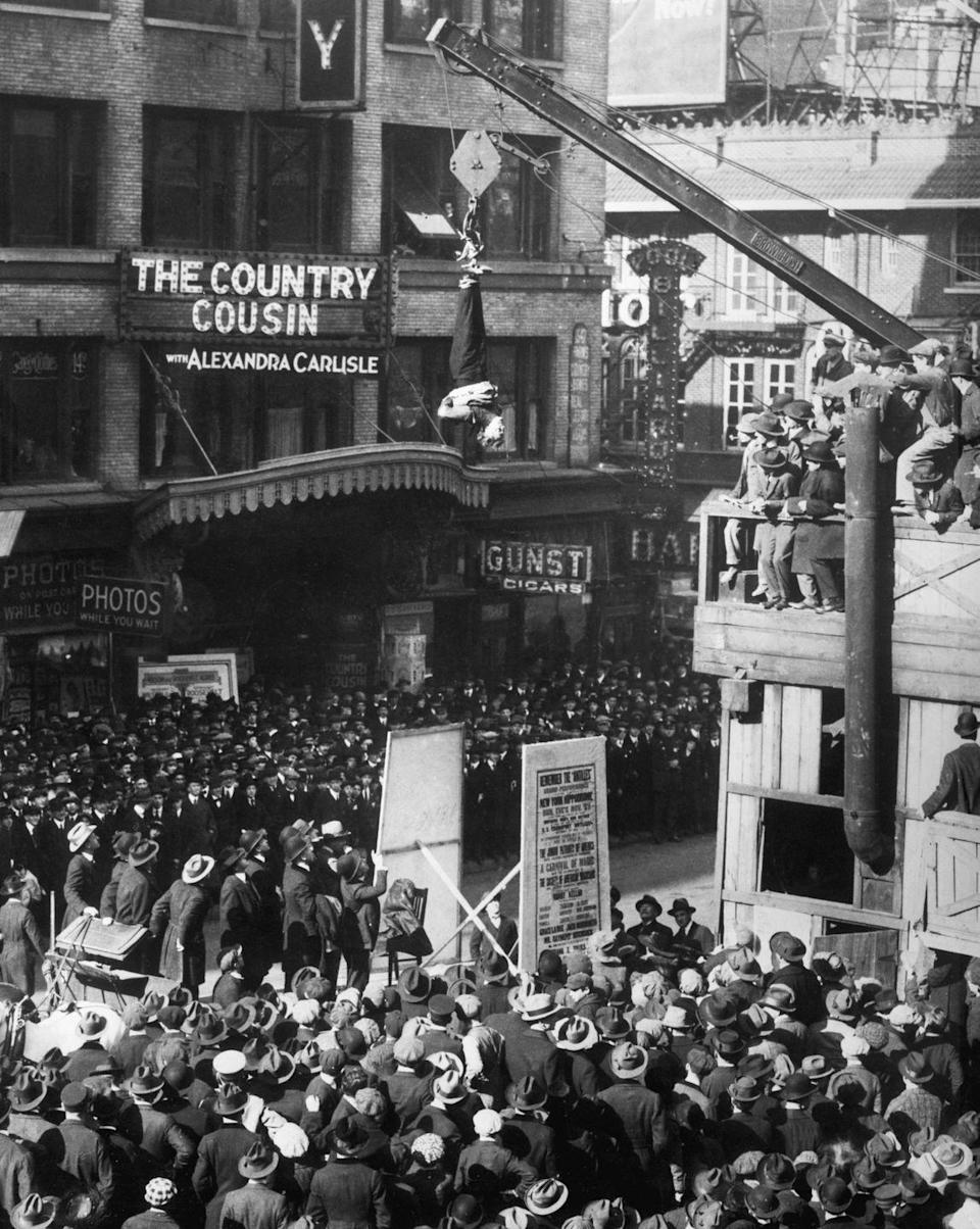 <p>Magician Harry Houdini attempts to escape from a straightjacket, while hanging upside down over the intersection of Broadway and 46th Street. </p>