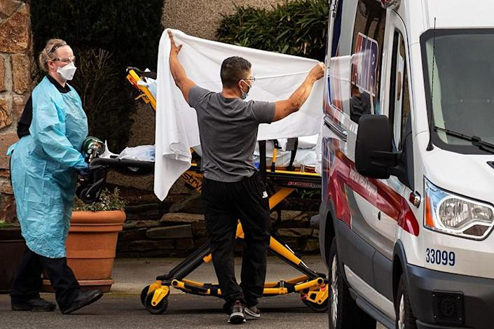 "Healthcare workers load a patient into an ambulance at Life Care Center in Kirkland, Wash. <span class=""copyright"">(Getty Images)</span>"
