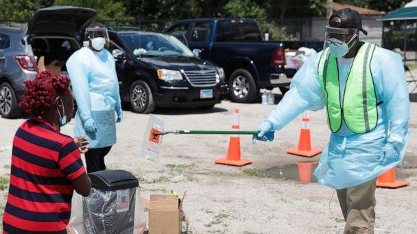 PHOTO: Workers help residents process a COVID-19 self-test at a mobile COVID-19 testing site set up in the Austin neighborhood of Chicago, June 23, 2020. (Scott Olson/Getty Images, FILE)
